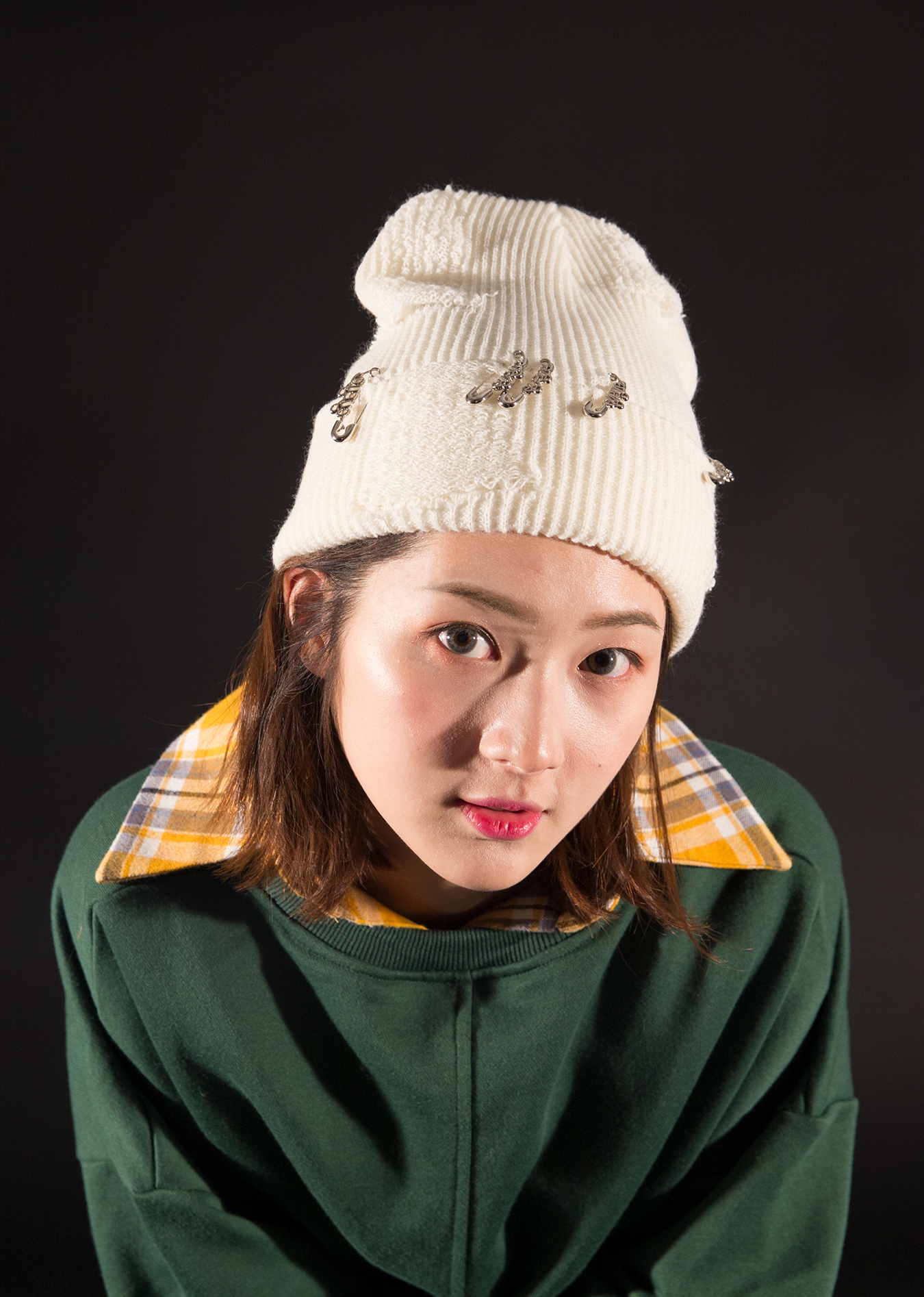 studio_white_hat_green_sweatshirt