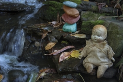 matt_garber_still_life_baby_doll_stack_stones_nature_depth_of_field_water_flow