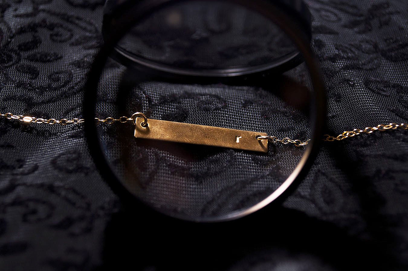 Rebecca_Huang_still_life_photography_dark_velvet_accessories_jewelry_lens_magnifying_reflection_gold_lettered_bar_necklace_chain_floral