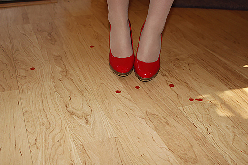 woman wearing red shoes and blood stained floor